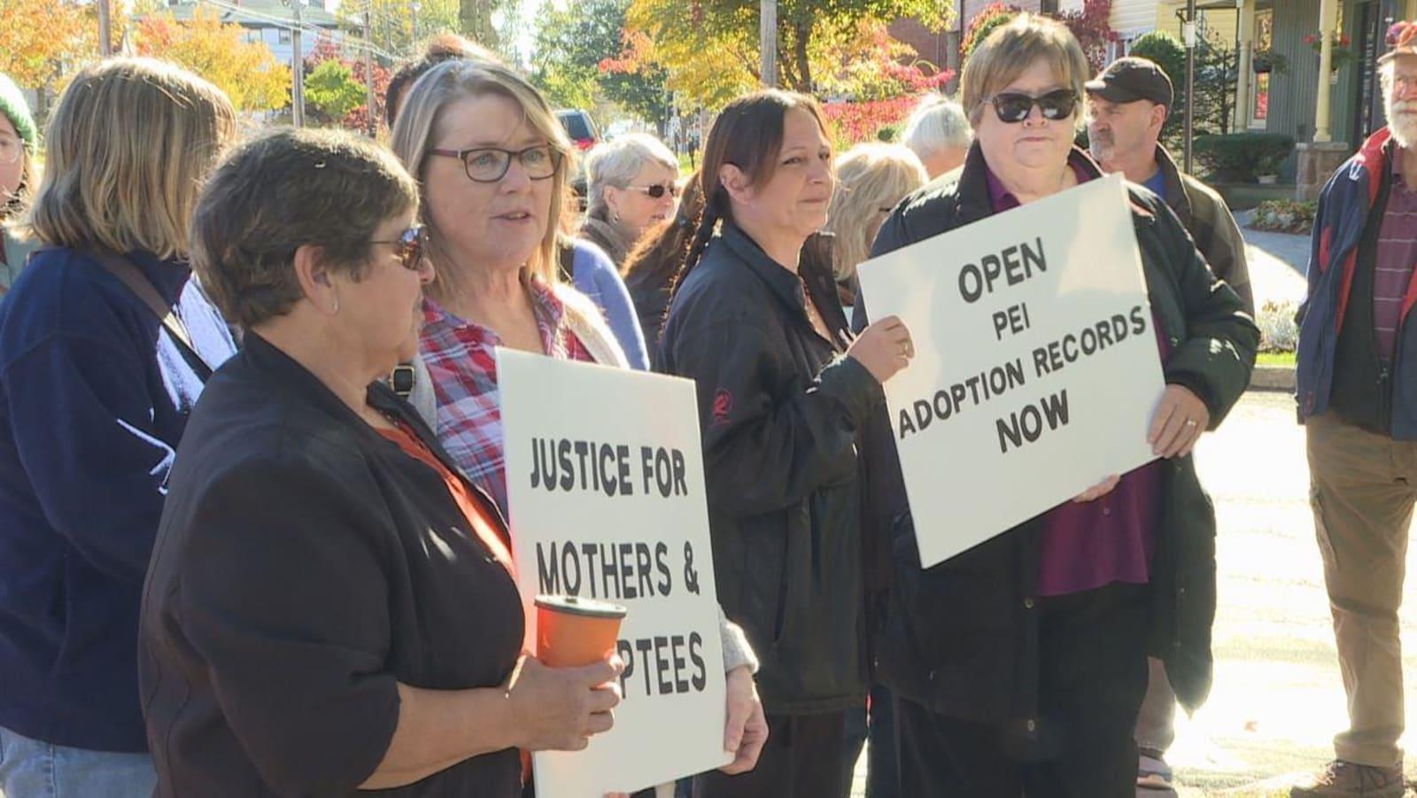 Des manifestants tiennent des pancartes et réclament «justice pour les mères et les personnes adoptées».