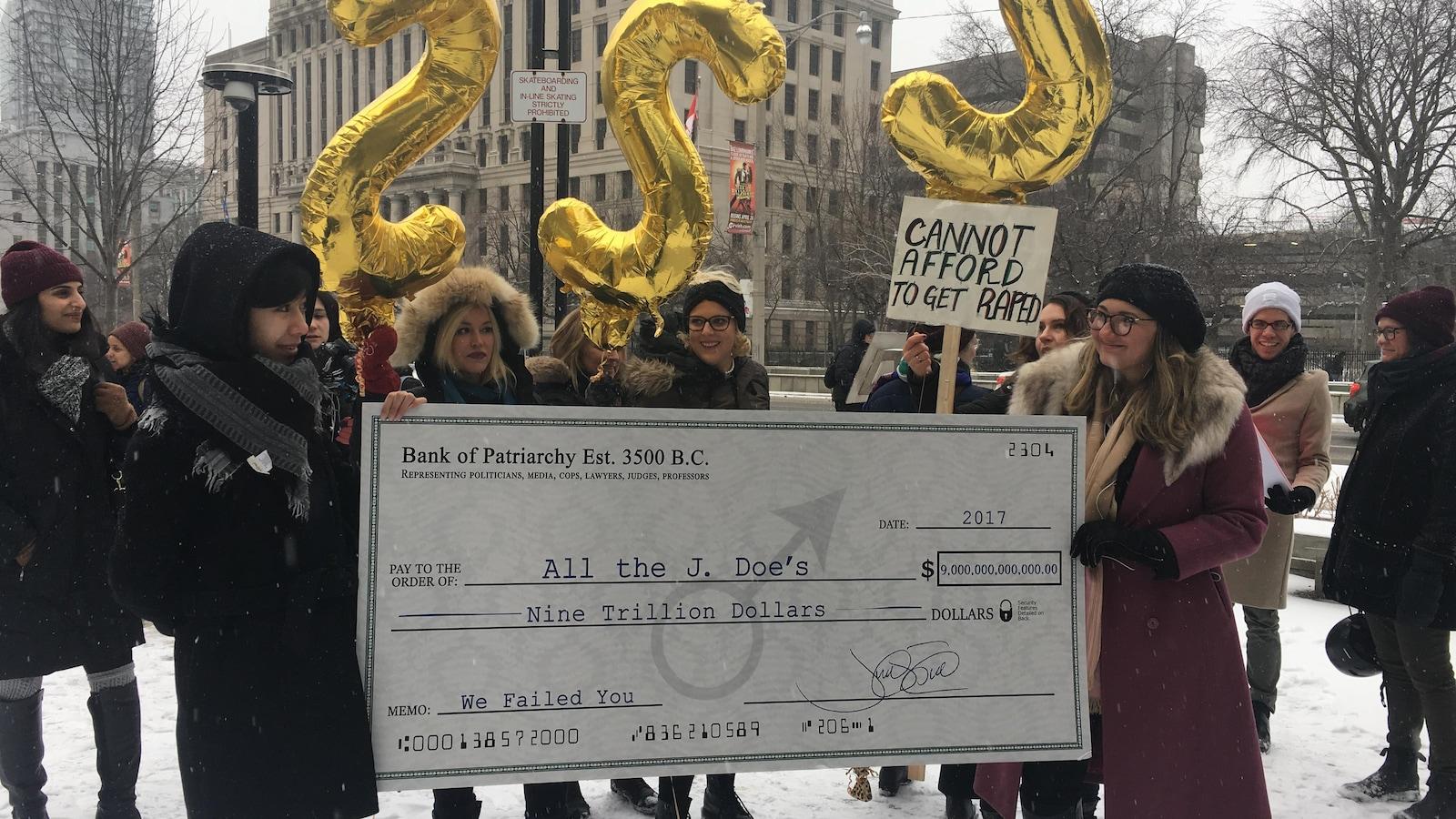 Des manifestantes tiennent un chèque géant pour réclamer des indemnités aux gouvernements.