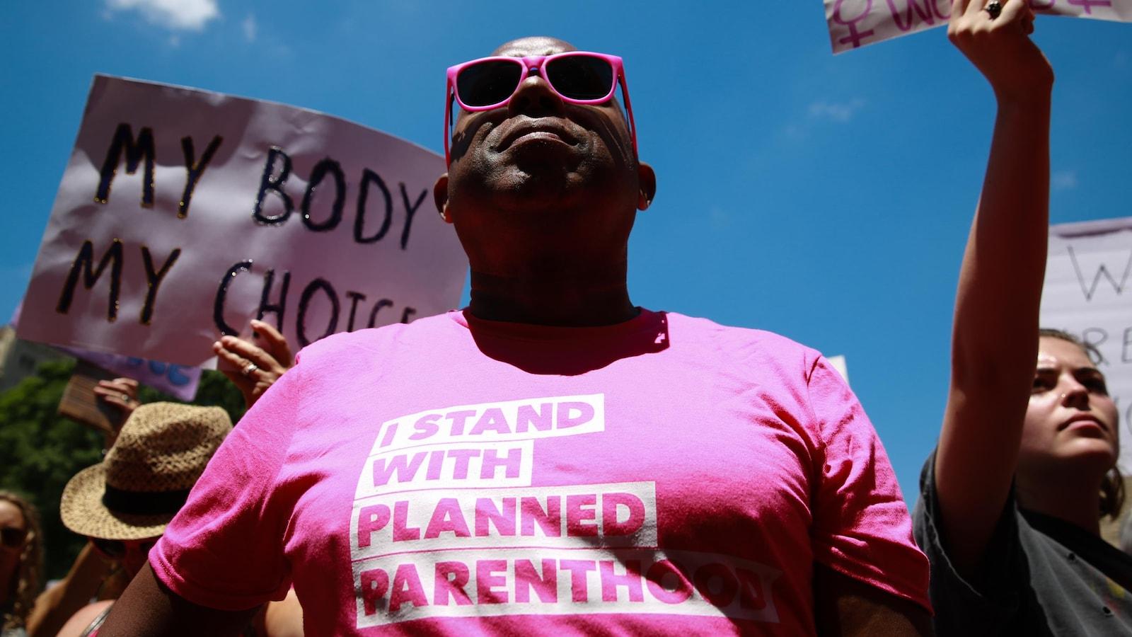 Un manifestant américain pro-choix porte un gaminet rose sur lequel il est écrit, en anglais : « Je soutiens Planned Parenthood ».