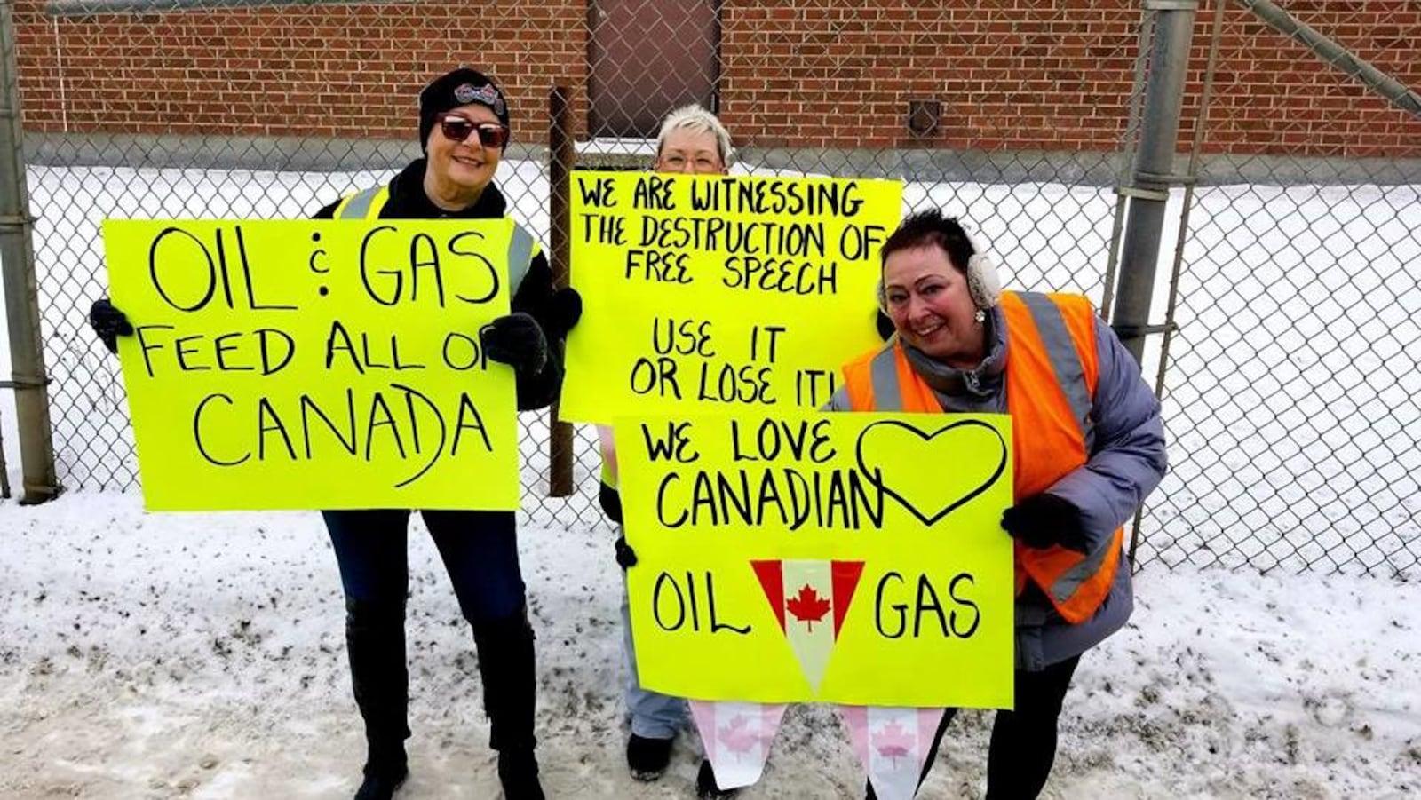 Trois manifestantes à Brandon debout sur la neige brandissent des pancartes qui appuient l'industrie pétrolière et gazière.