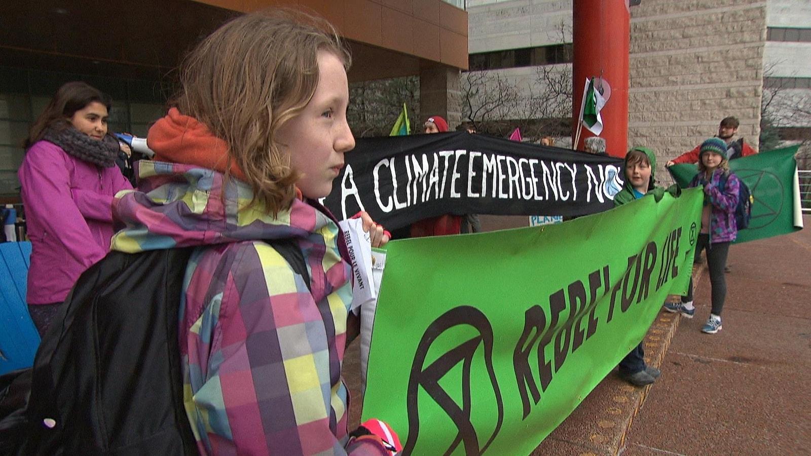 Des enfants tiennent des banderoles à l'entrée de l'hôtel de ville