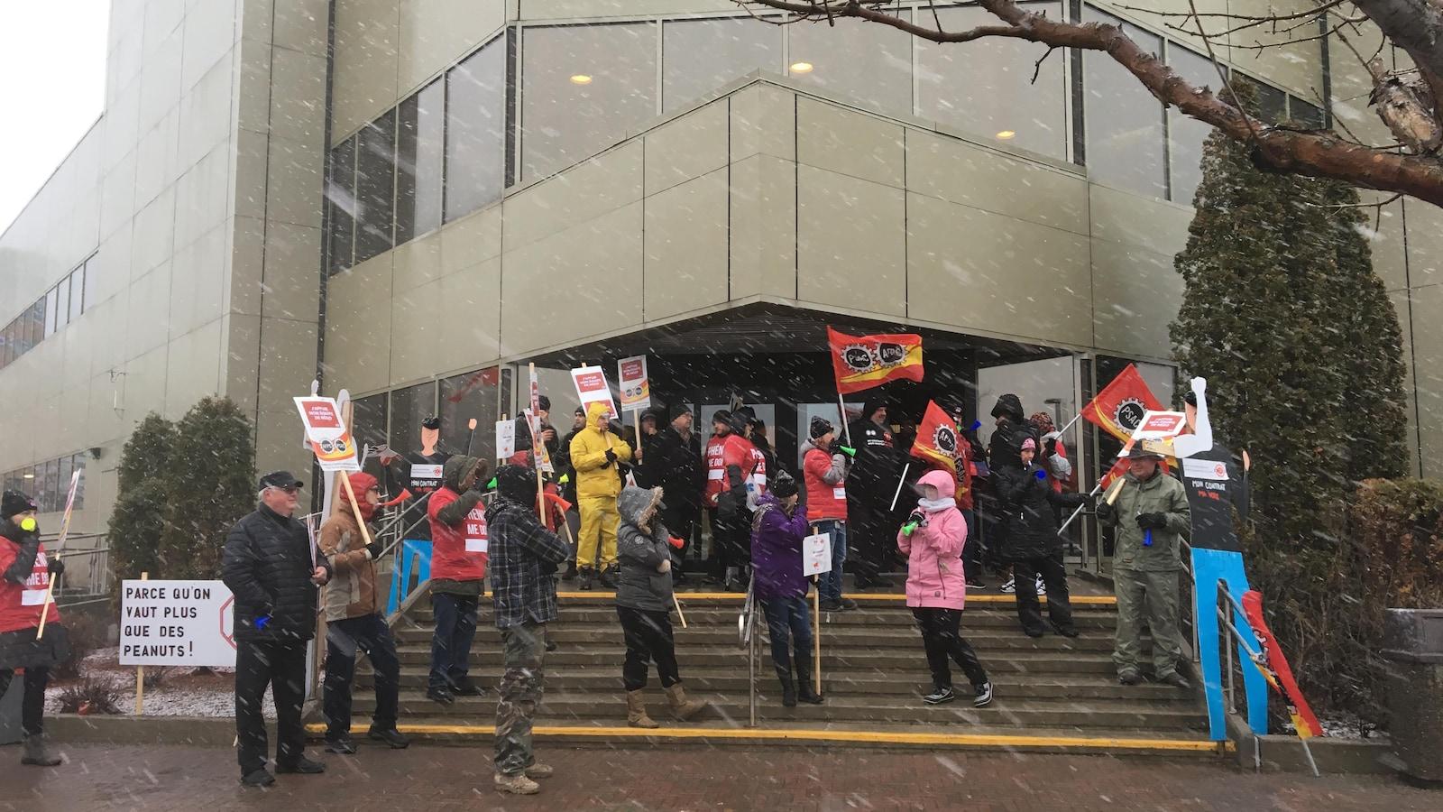 Des employés du gouvernement fédéral brandissent des pancartes devant l'édifice Lafontaine.