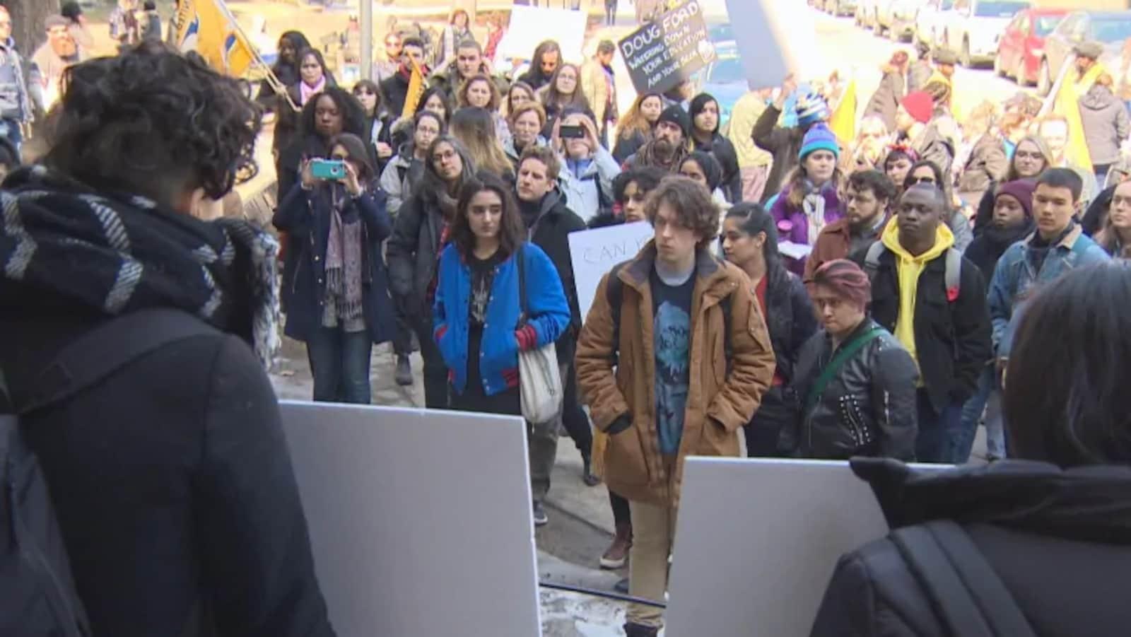 Des dizaines d'étudiants sont rassemblés et tiennent des pancartes dénonçant la politique de Doug Ford.
