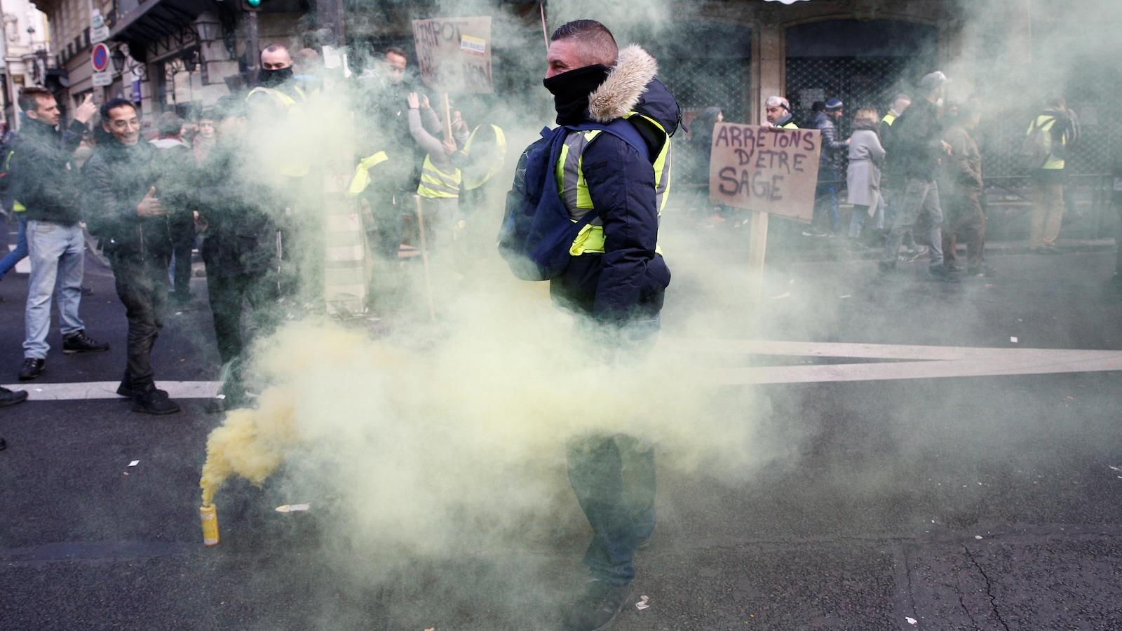 Un manifestant en gilet jaune dans une nuage de fumigène.