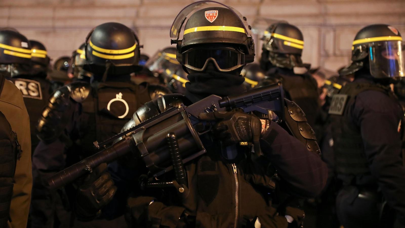 Un membre des forces anti-émeutes portant un lanceur de grenades de gaz lacrymogène à Paris lors d'une manifestation des gilets jaunes.