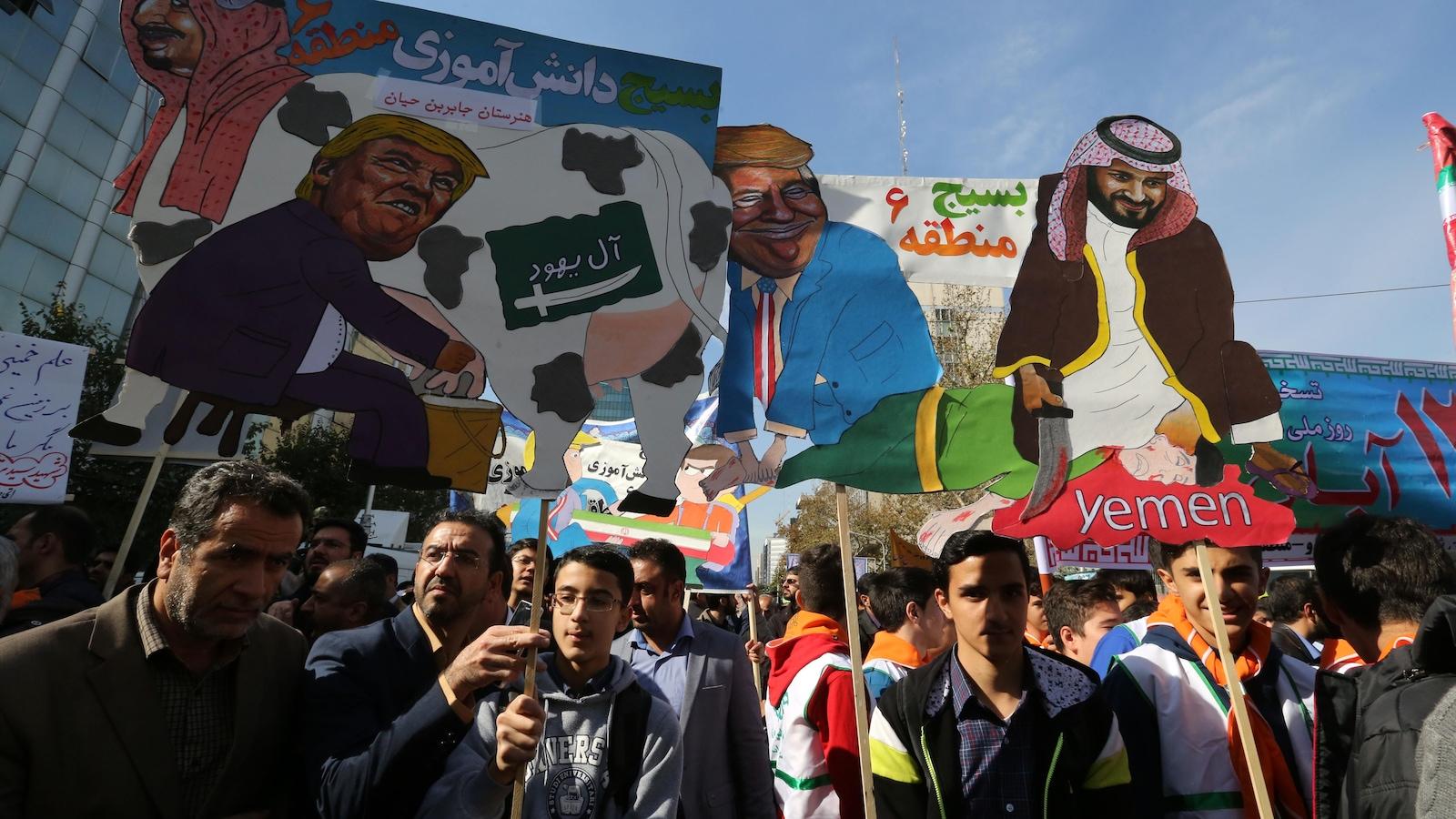 Des manifestants brandissant des caricatures montrant le président américain Donald Trump en train de traire le lait d'une vache frappé d'un drapeau saoudien sur le côté et portant la tête du roi Salmane d'Arabie saoudite.