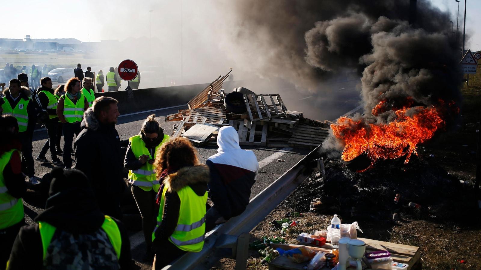 Un blocage routier avec un incendie et des citoyens arborant un gilet jaune.