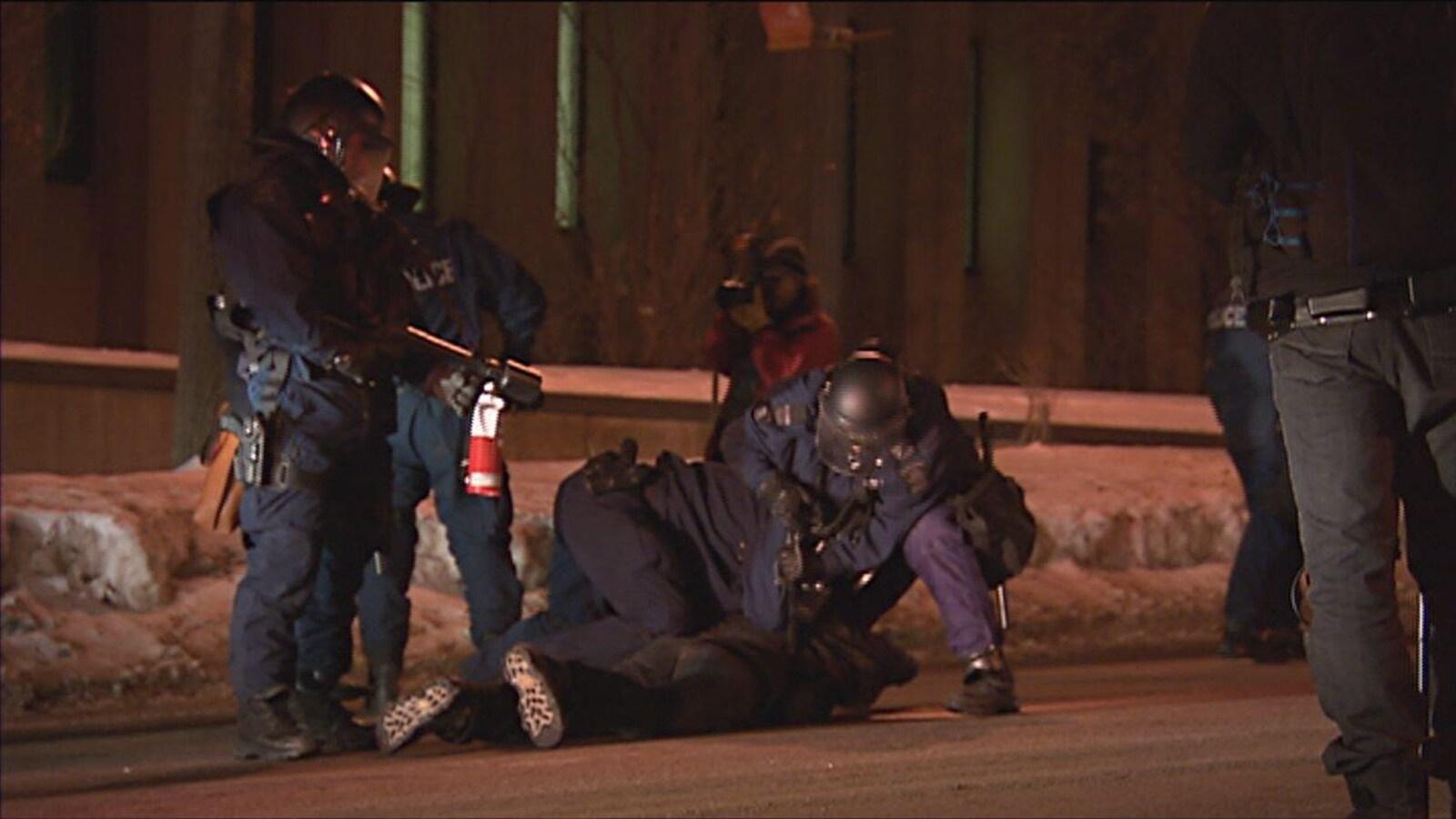 Des policiers arrêtent un manifestant.