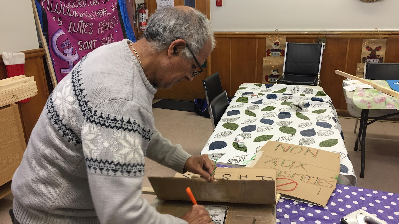 Un homme écrit sur une pancarte en carton