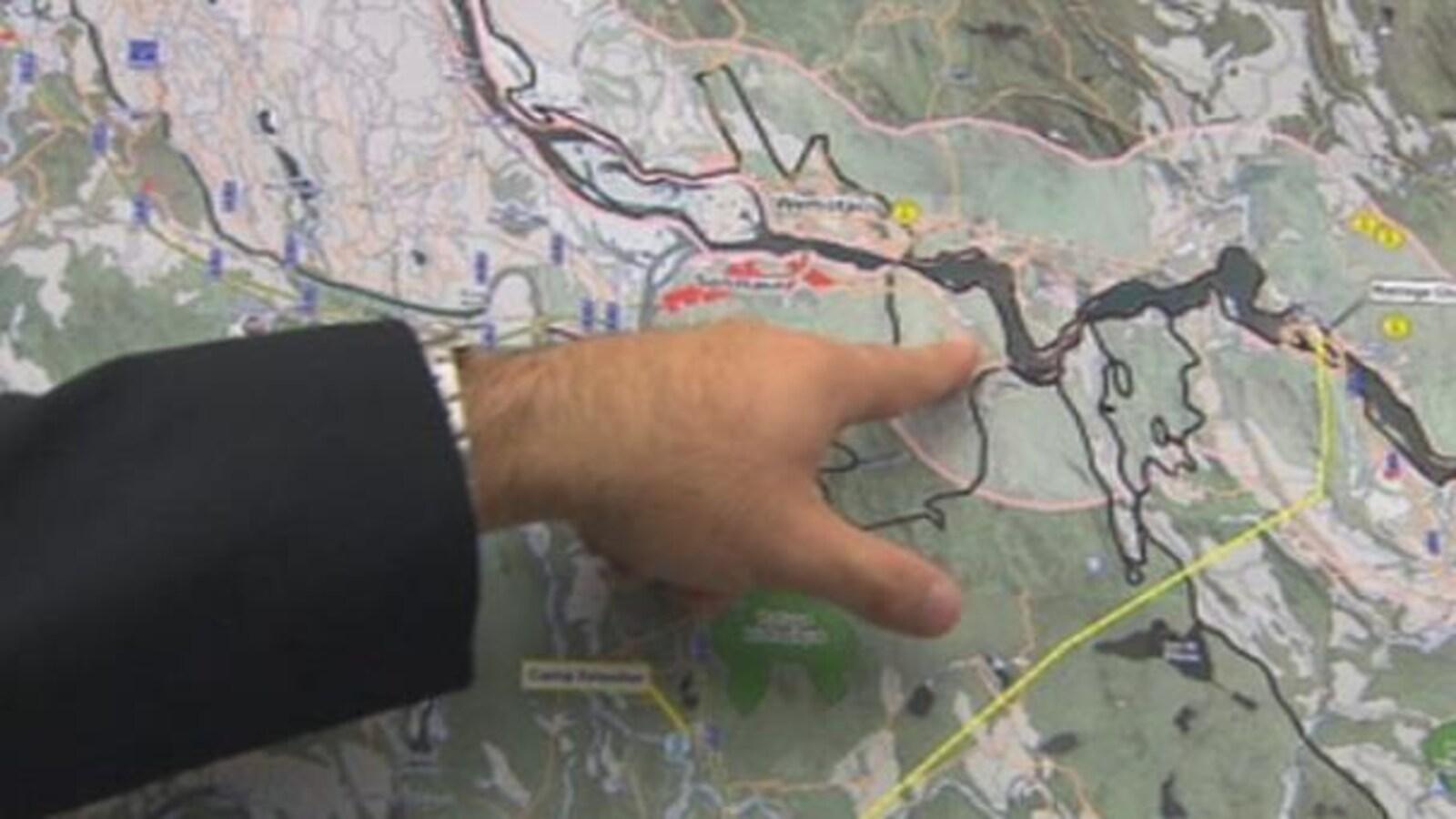 Une main pointe une rivière sur une carte.