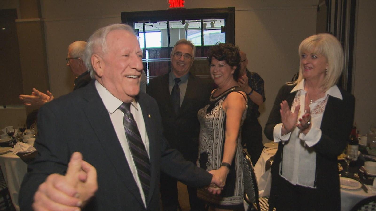 Un homme âgé souriant serre des mains à des personnes réunis dans une salle.