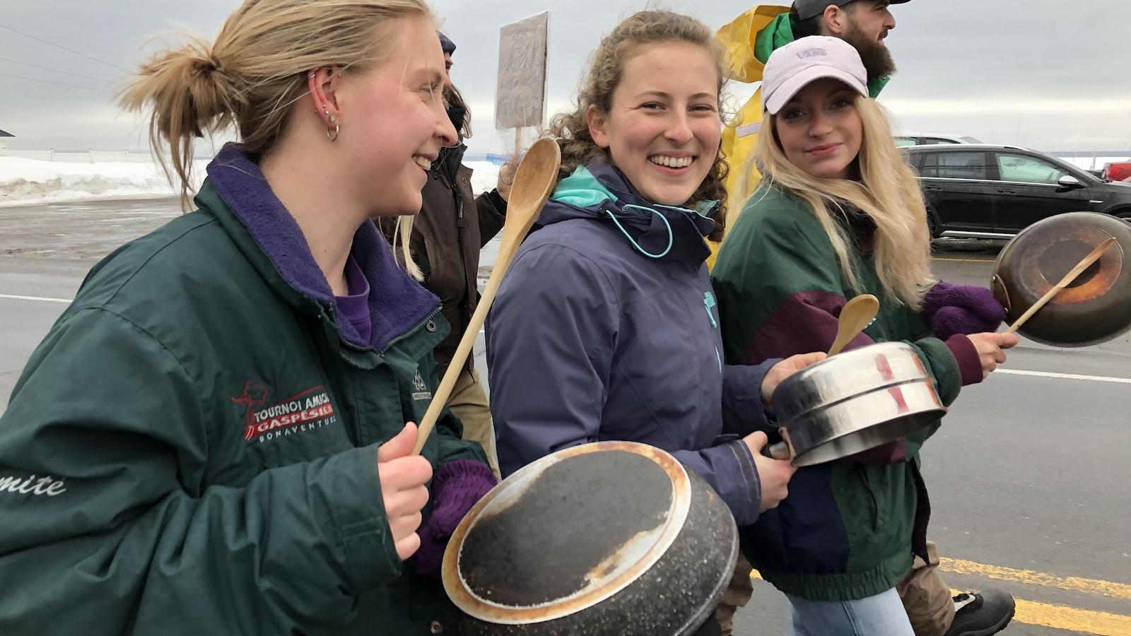 Trois jeunes filles sourient à la caméra en tapant sur des casseroles avec des cuillères de bois.