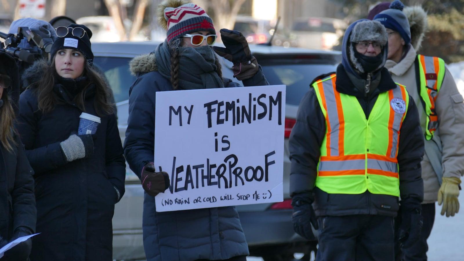 Une femme, portant un manteau d'hiver et des lunettes, brandit une pancarte qui dit, en anglais : « My feminism is Weatherproof », suivi de l'inscription « no rain or cold will stop me », autrement dit « ni la pluie ni le froid ne vont m'arrêter ». Elle est entourée d'autres femmes et de membres de la patrouille communautaire Bear Clan.
