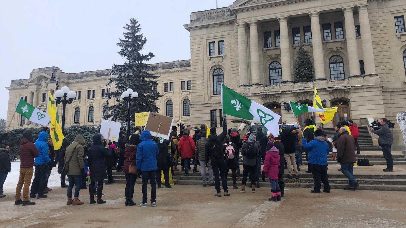Des dizaines de personnes sont rassemblées devant l'Assemblée législative de la Saskatchewan. Elles brandissent des pancartes et des drapeaux fransaskois et franco-ontariens.