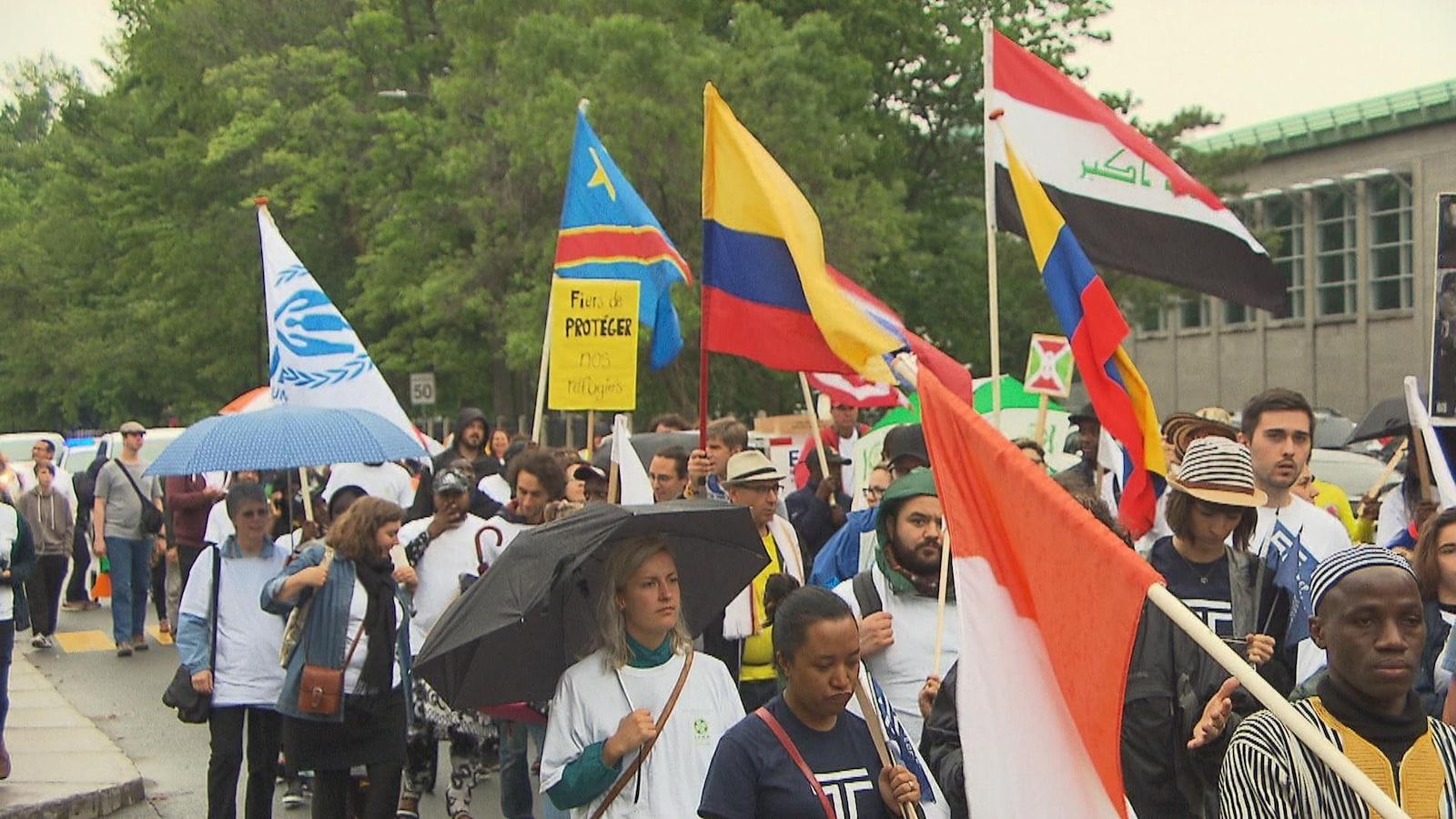 Plusieurs personnes marchent dans la rue par une journée grise. Certains brandissent des drapeaux aux couleurs de leur pays d'origine.