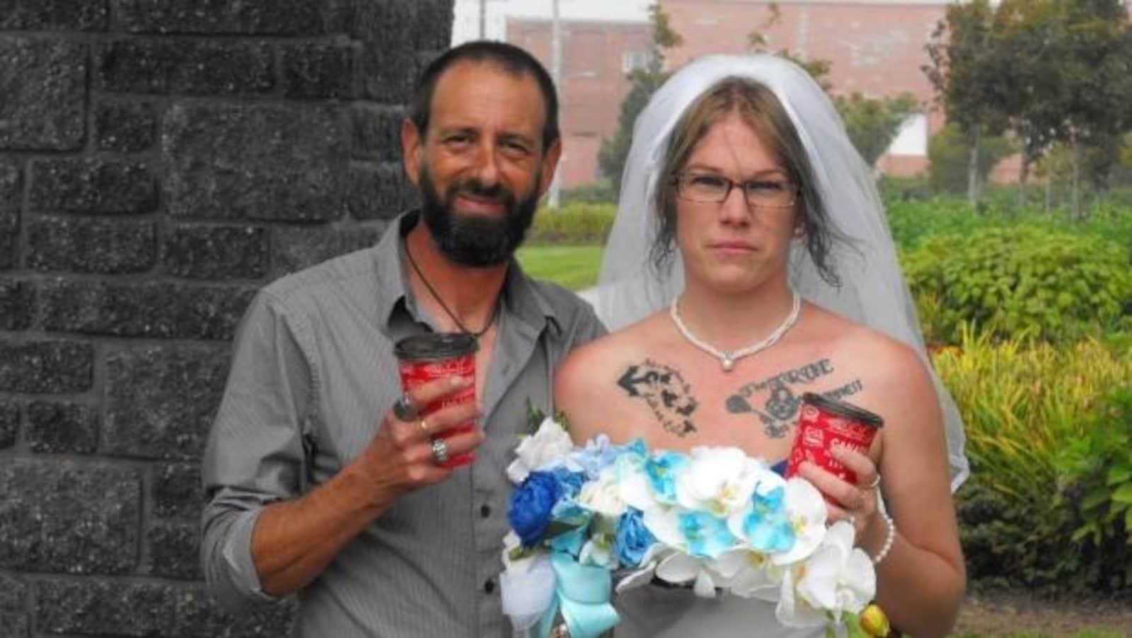 Les nouveaux mariés avec des tasses de Tim Hortons à la main.