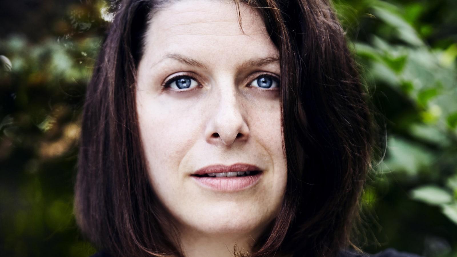 Portrait de la poète Marie-Hélène Voyer avec du feuillage vert en arrière-plan. Elle porte un t-shirt noir décolleté à manches courtes et des cheveux auburn au carré sous le menton.