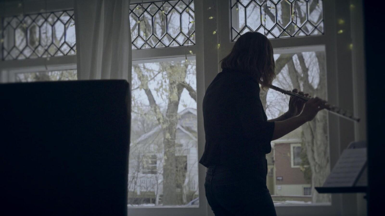 La musicienne Marie-Véronique Bourque joue de la flûte traversière de dos devant une fenêtre.