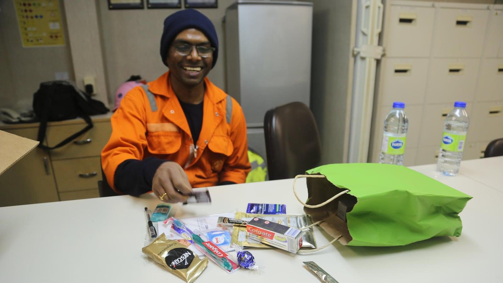 Un homme sourit devant des objets étalés sur une table devant lui. On peut y voir du dentifrice, des brosses à dents et des stylos.