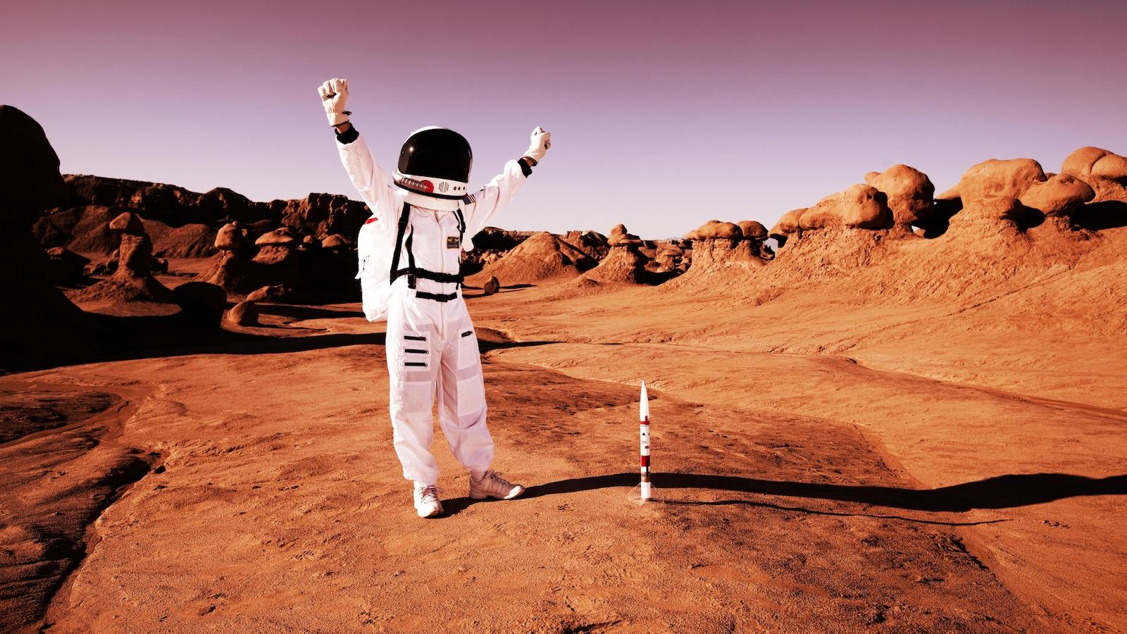 Image représentant un astronaute faisant le signe de la victoire sur une surface rouge ressemblant à celle de la planète Mars.