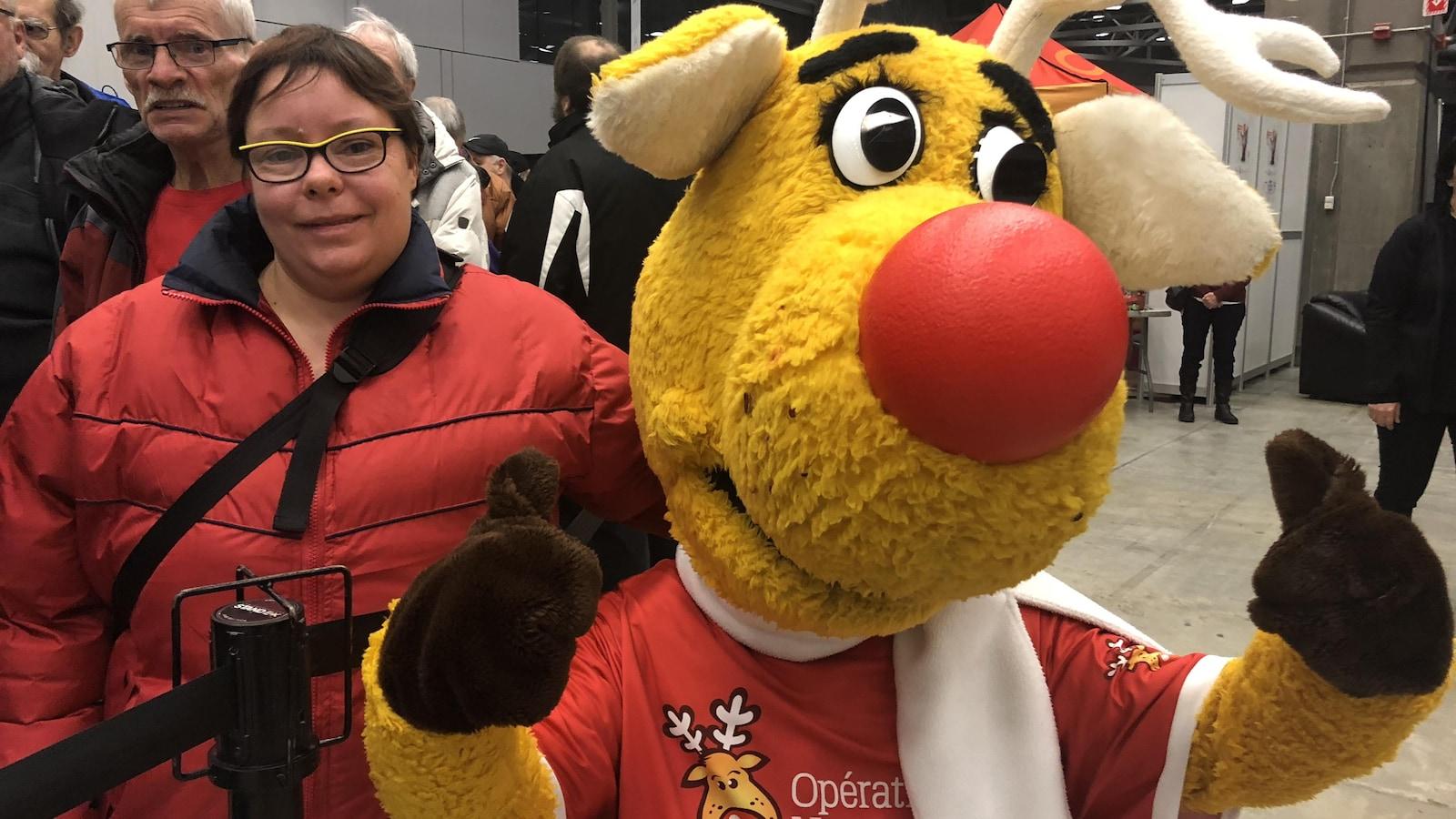 La mascotte d'Opération Nez rouge accompagnée d'une bénévole.
