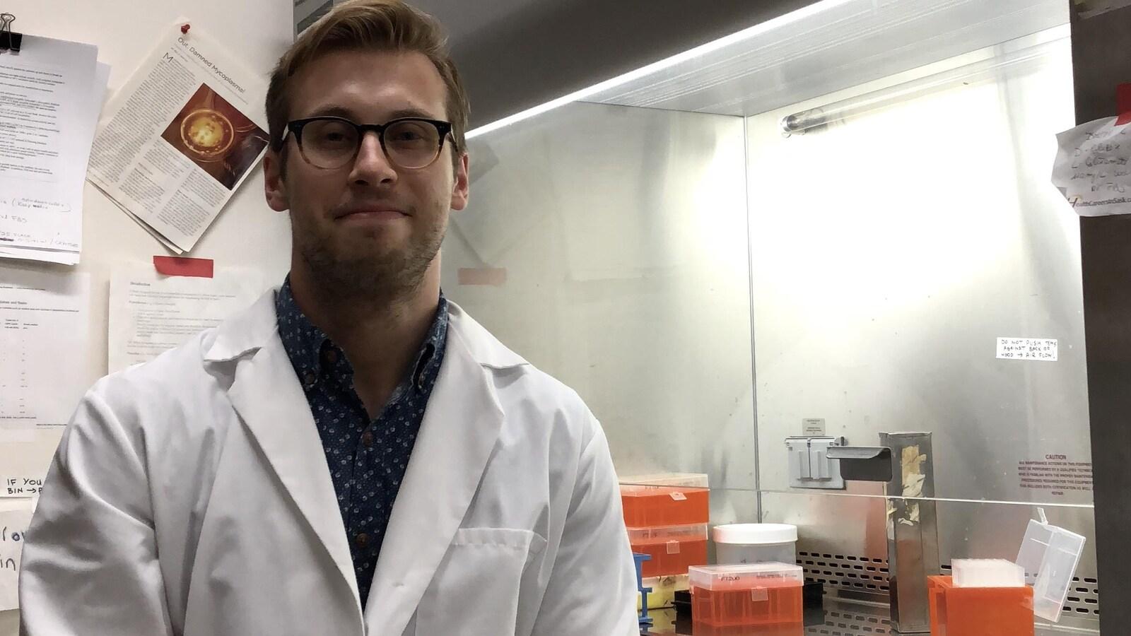 Matt Anderson-Baron est vêtu d'un sarrau, assis dans son laboratoire.