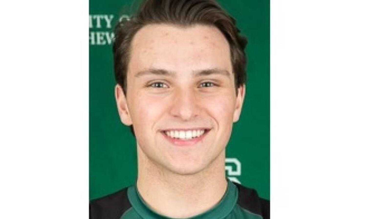Le jeune homme porte fièrement le chandail de l'équipe de volleyball de l'Université de la Saskatchewan.