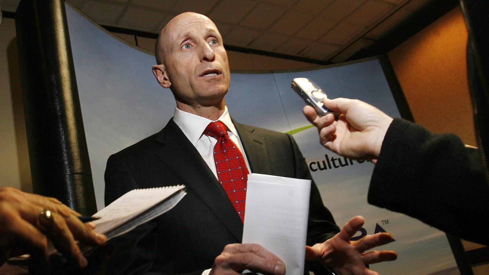 Mayo Schmidt en complet se tient devant des journalistes qui ont une enregistreuse et un calepin.