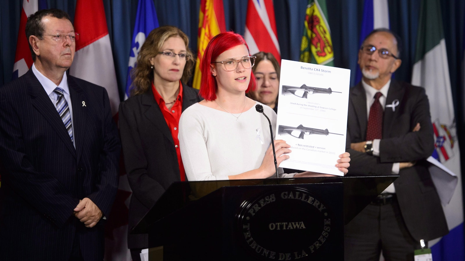 Une jeune fille aux cheveux rouges tient une image d'armes à feu lors d'une conférence de presse.