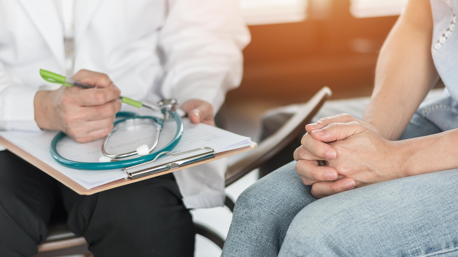 Une femme consulte un médecin, qui prend des notes.