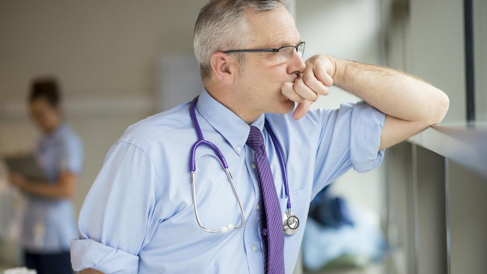 Un médecin épuisé prend une pause pour regarder dans le néant.