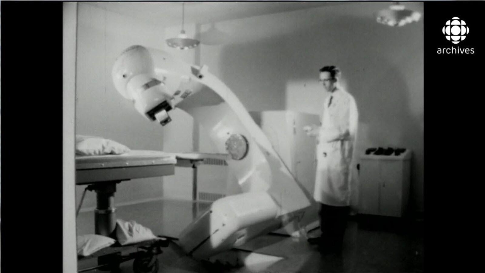 Homme en sarrau manipulant à l'aide d'une manette un gros appareil de médecine nucléaire qui entame une rotation