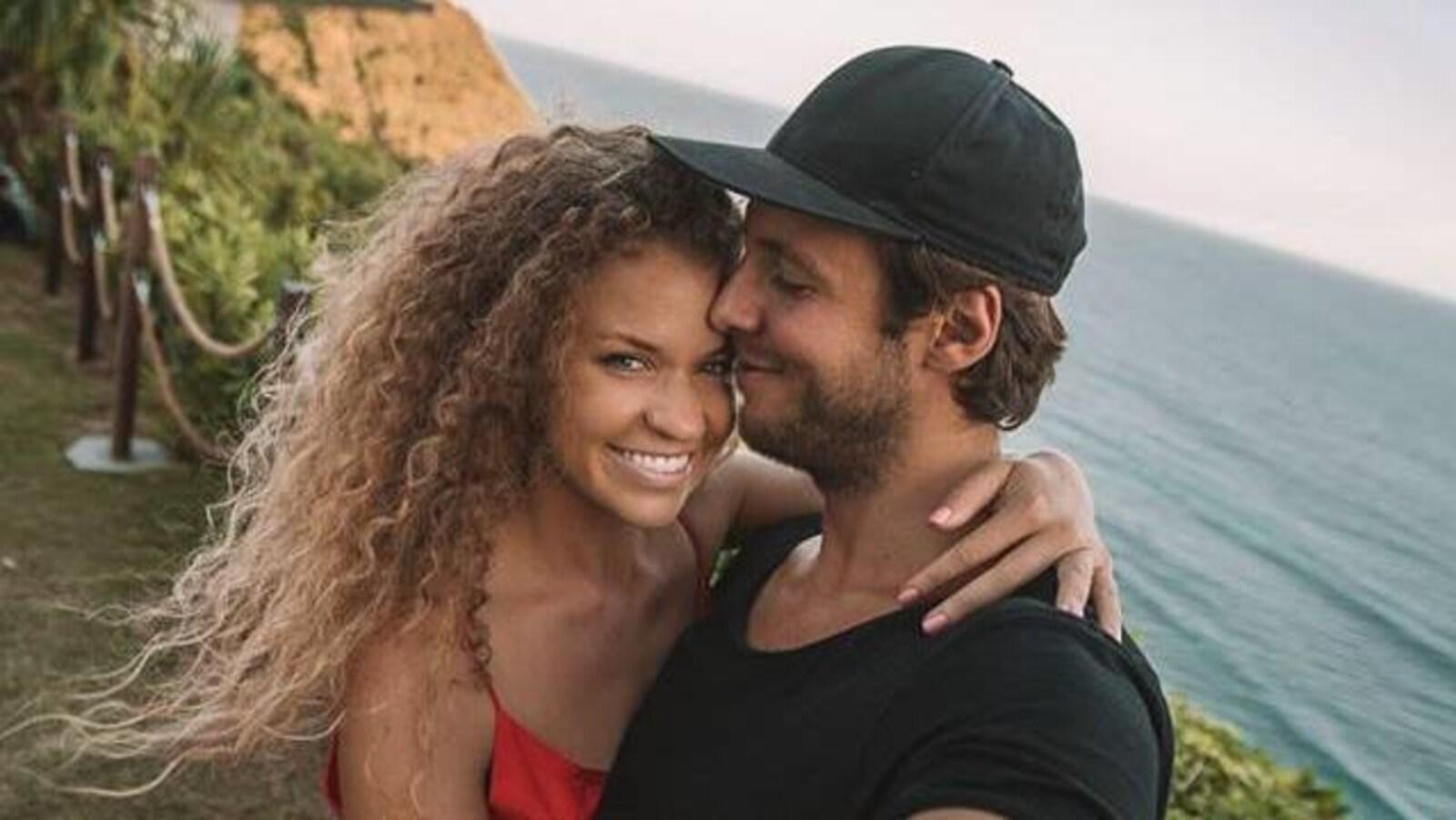 Une femme en robe rouge et un homme en t-shirt noir au bord de la mer.