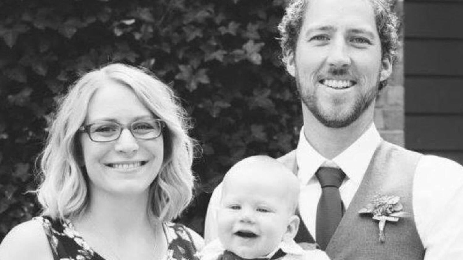 Portrait de famille en noir et blanc avec Mélanie Hugues (à gauche), son mari (à droite) et leur bébé Winston dans ses bras.