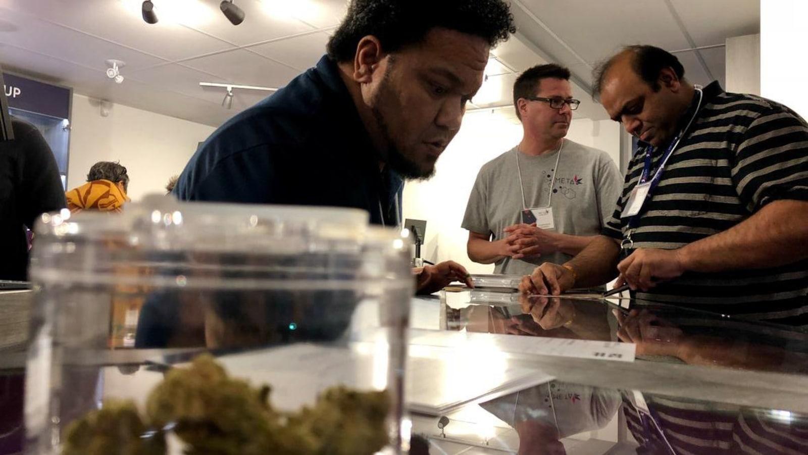 Trois hommes regardent une liste de produits sur un comptoir avec, à l'avant-plan, un pot contenant des cocottes de cannabis.