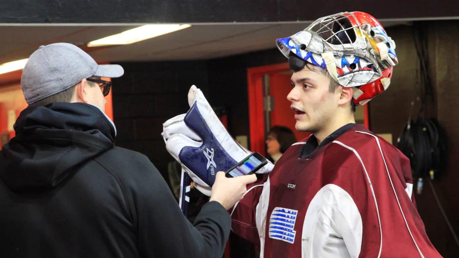 Une jeune homme vêtu d'un équipement de hockey donne une entrevue à un journaliste qui tient son téléphone devant le jeune homme.