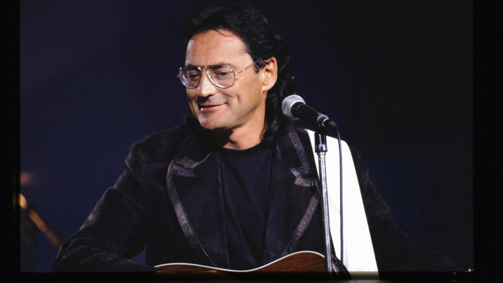 Le musicien est sur scène et sourit devant un micro.