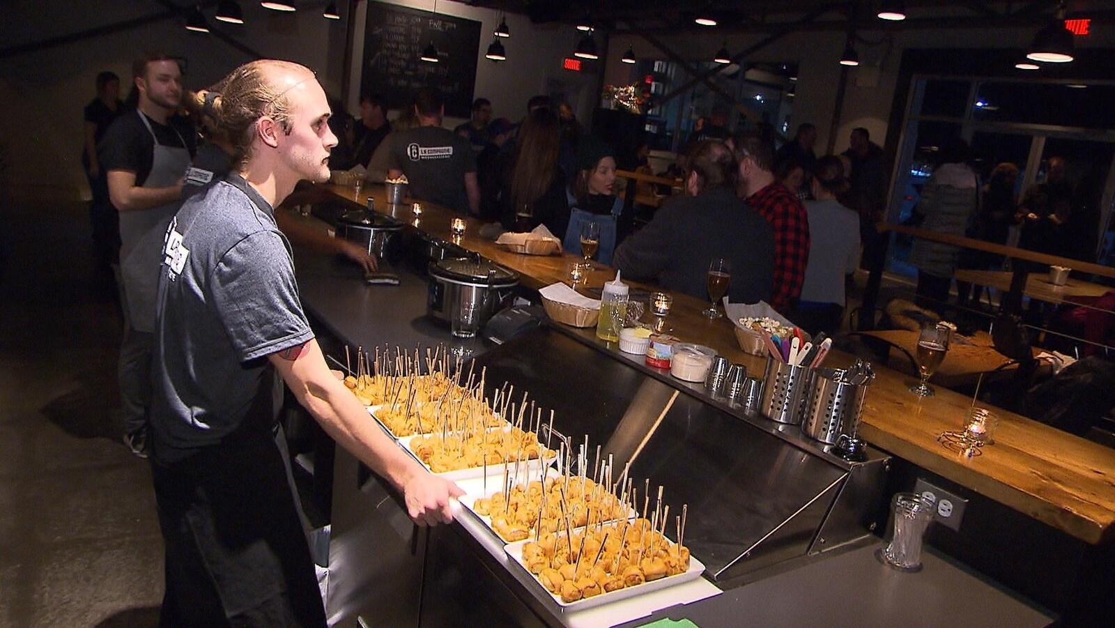Un serveur dans une brasserie avec des hors d'oeuvre pour la dégustation de La Compagnie, une nouvelle bière artisanale à Sept-Îles