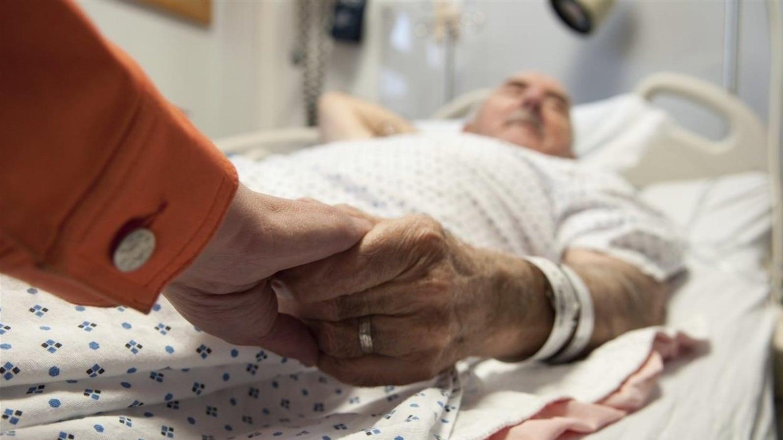 Un homme âgé est couché les yeux fermés dans un lit et tient la main d'un proche.