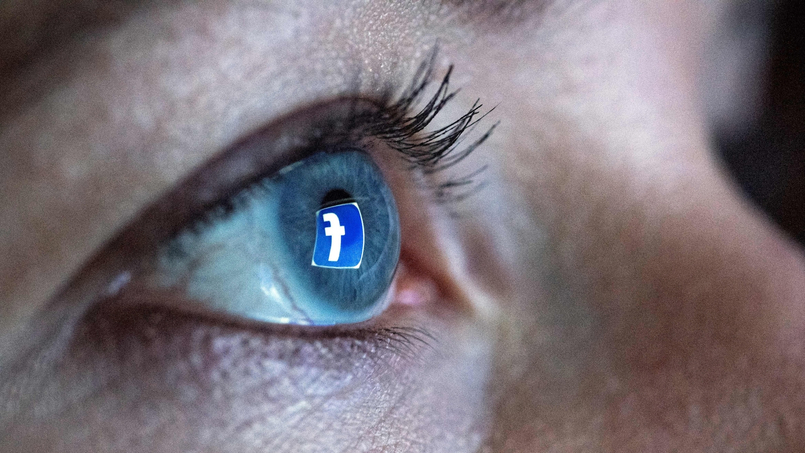 Une femme se tient devant un écran d'ordinateur alors que le logo du réseau social Facebook se réflète dans son œil.