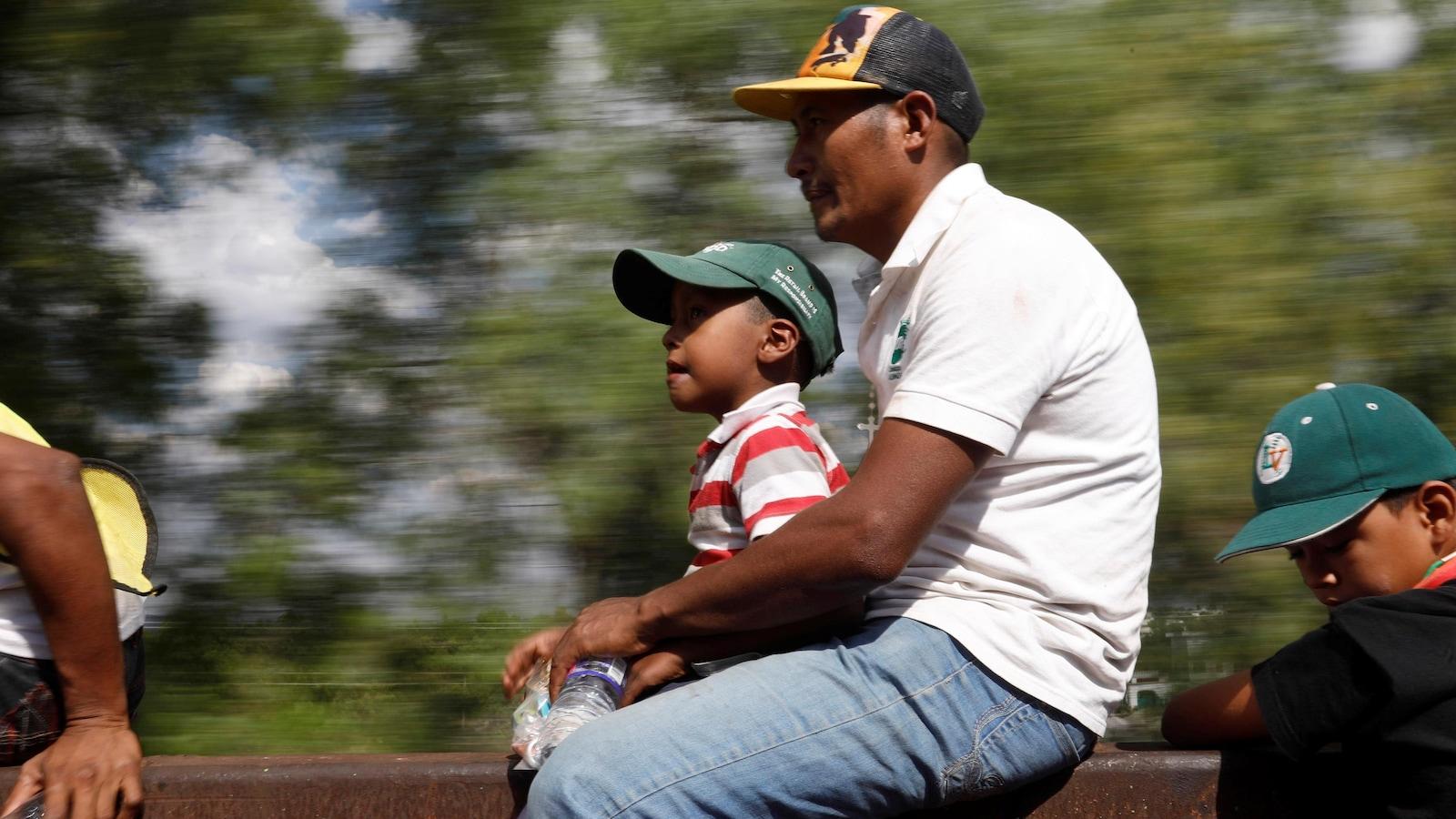 Un homme et un jeune garçon sont assis sur un wagon de train.