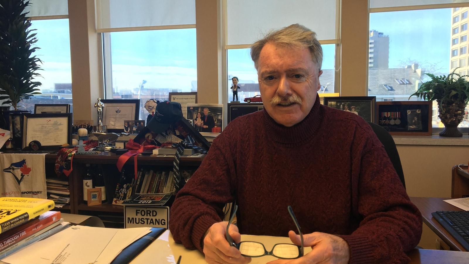 Un homme assis à un bureau tient ses lunettes dans ses mains en regardant l'objectif de la caméra. On peut voir derrière lui plusieurs de ses effets personnels comme des cadres et des médailles.