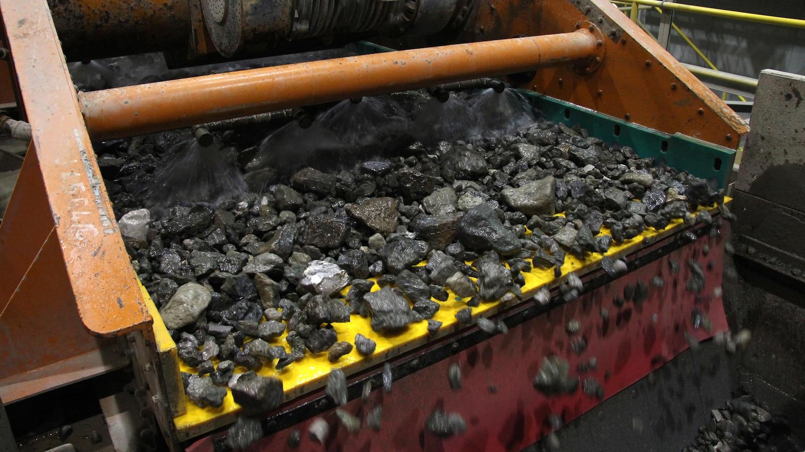 Des roches scintillantes sont aspergées par une machine.