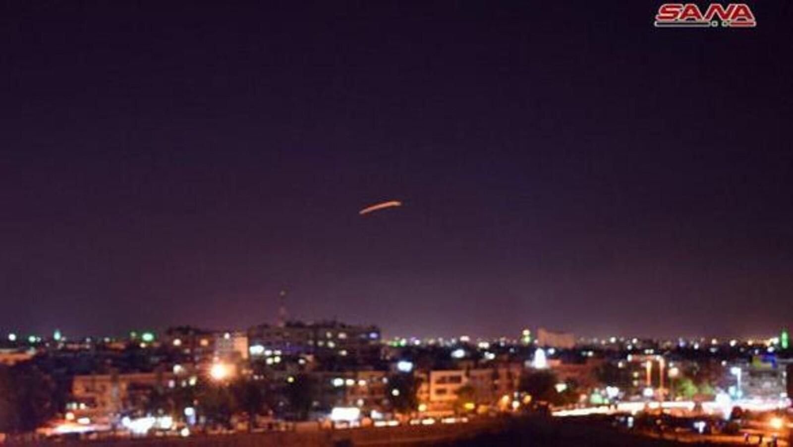 Damas est éclairée par les lumières de la ville. En pleine nuit, un tir de missile est visible dans le ciel, au loin.