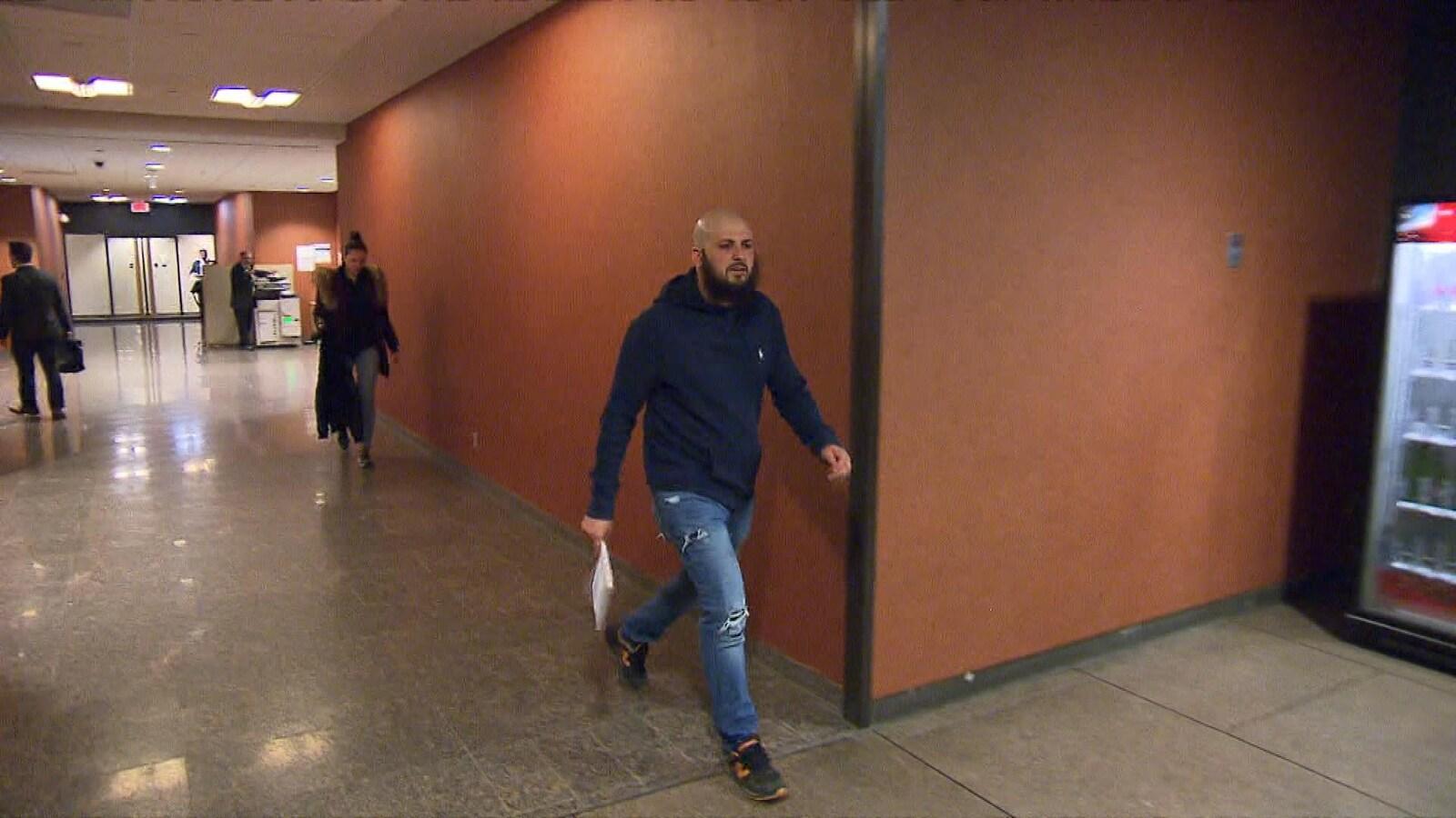 Mohamed Taleb tenant des feuilles entre ses mains dans un couloir du palais de justice.