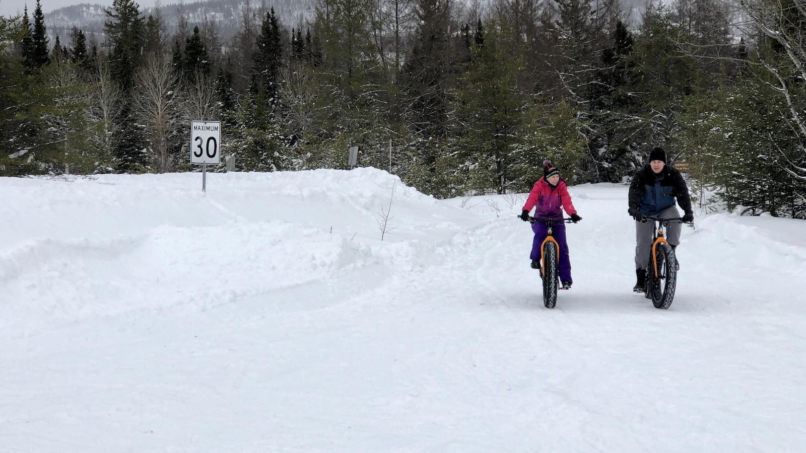 Deux citoyens circulent en vélo à neige au Parc nationale des Monts-Valin.