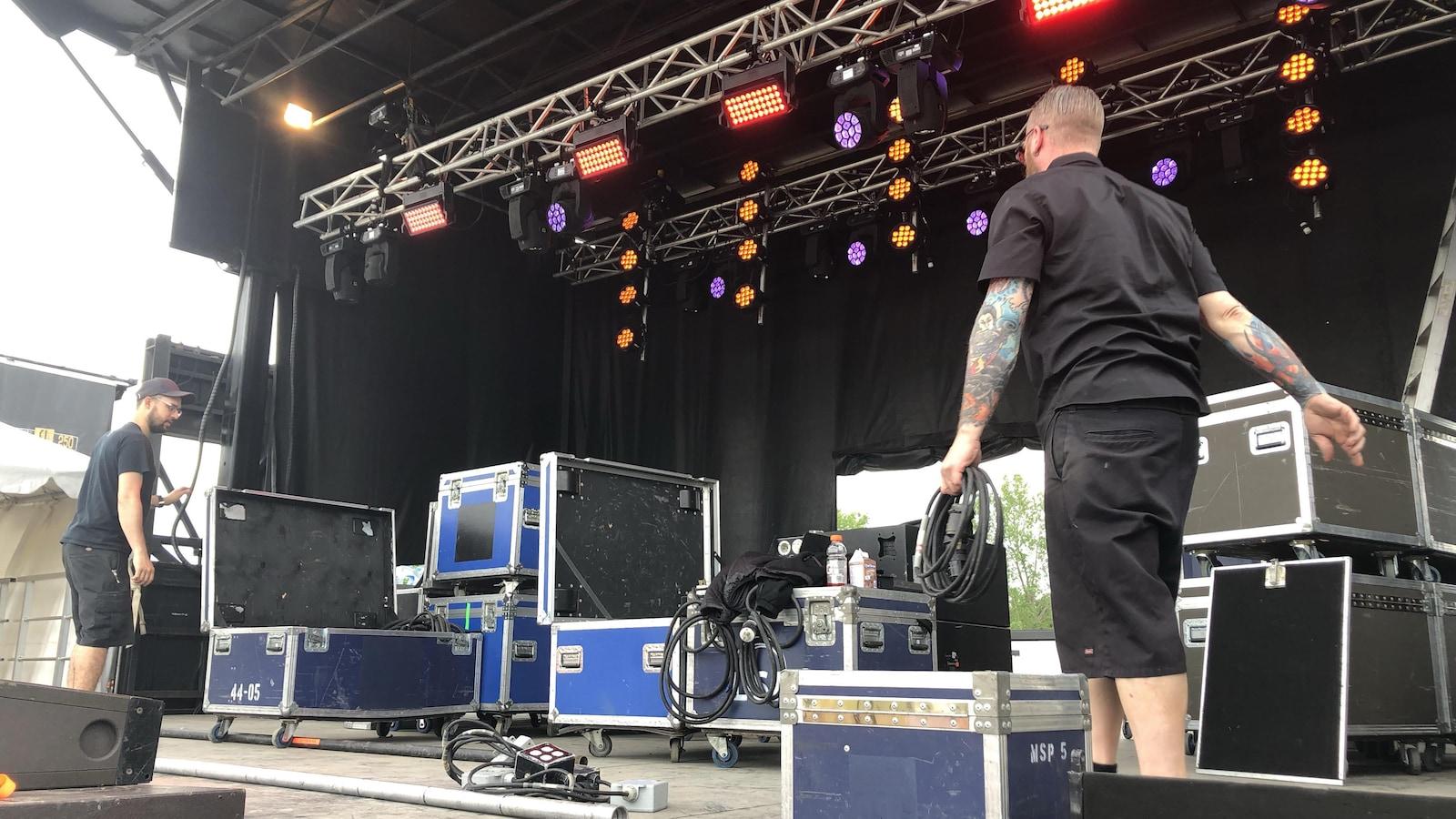 Des hommes déplacent de l'équipement et des caisses de matériel sur une scène.