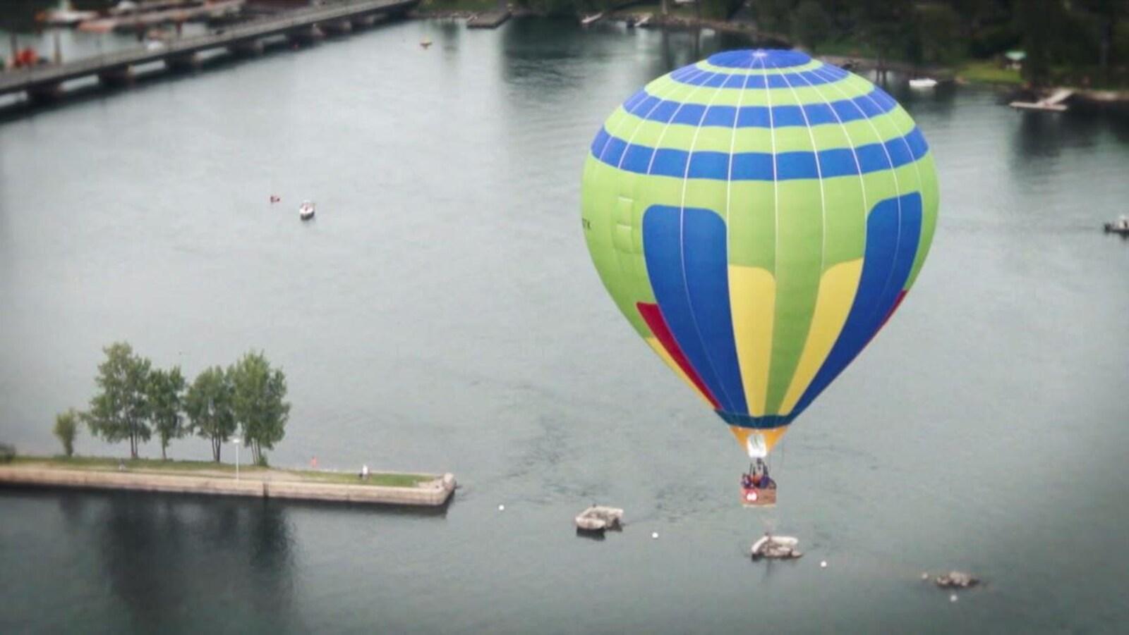 Une montgolfière dans le ciel au-dessus d'un plan d'eau