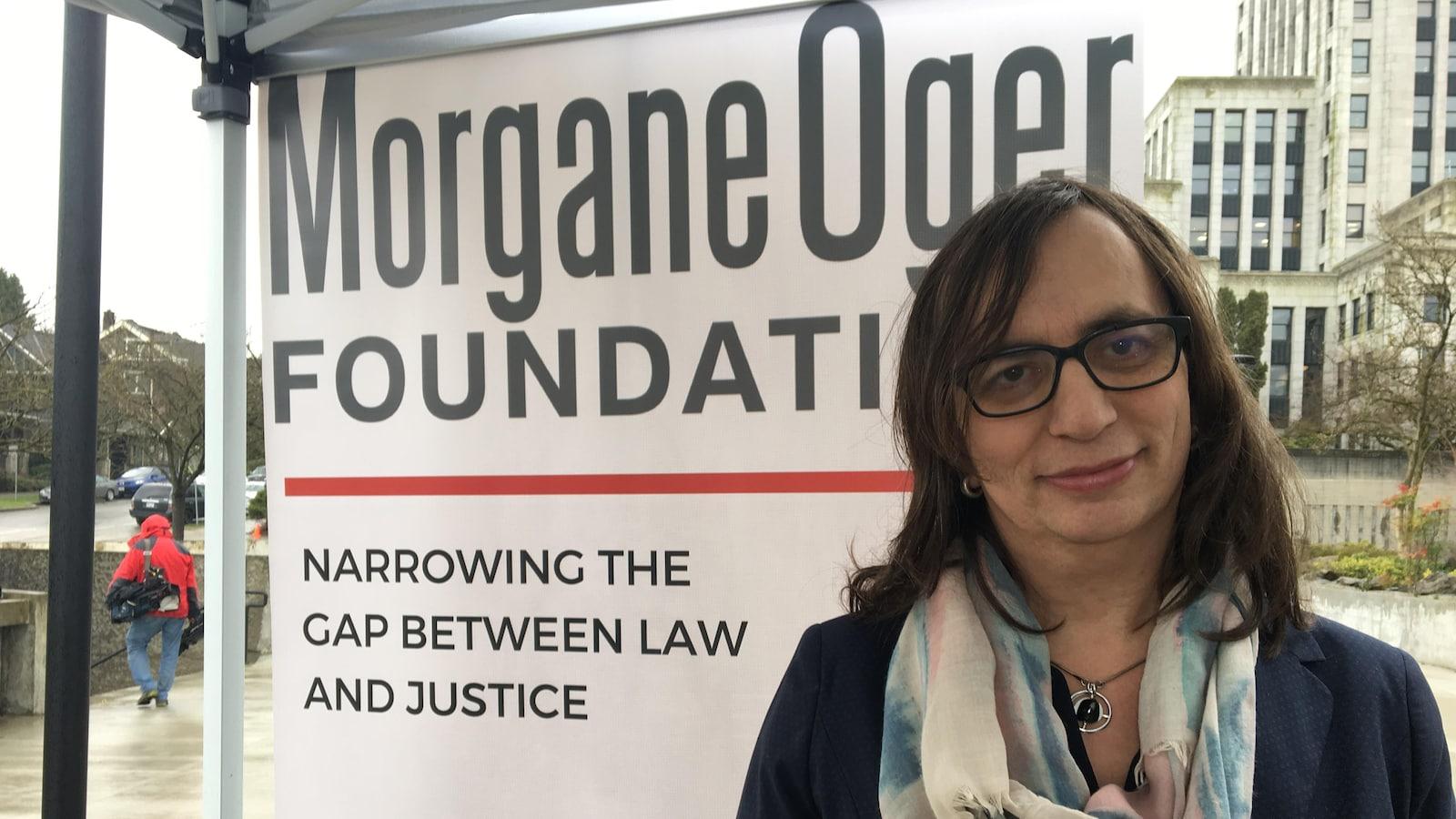 Morgane Oger, une femme transgenre, pose à l'extérieur devant une affiche sur laquelle il est inscrit Morgane Oger Foundation. Elle porte des lunettes, des cheveux bruns aux épaules et un foulard aux couleurs pâles.