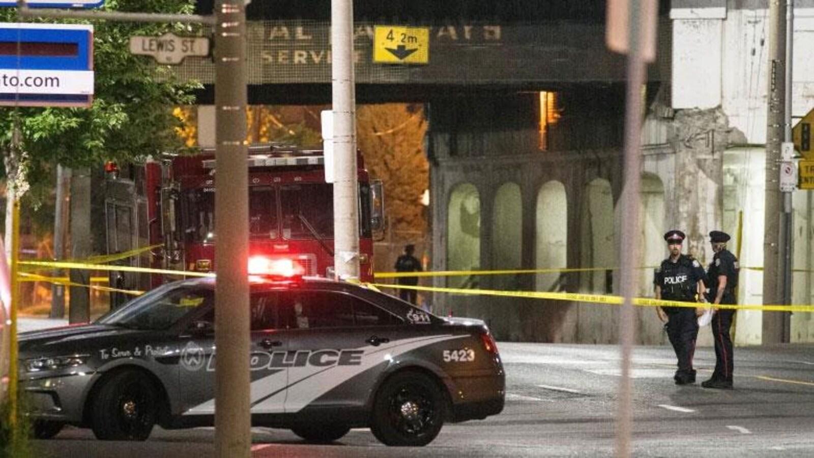 Une voiture de police et deux policiers dans une rue la nuit